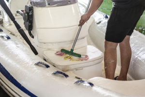 Echuca Moama Boat and Storage Solutions. Image of a man washing the interior of a boat with a mop