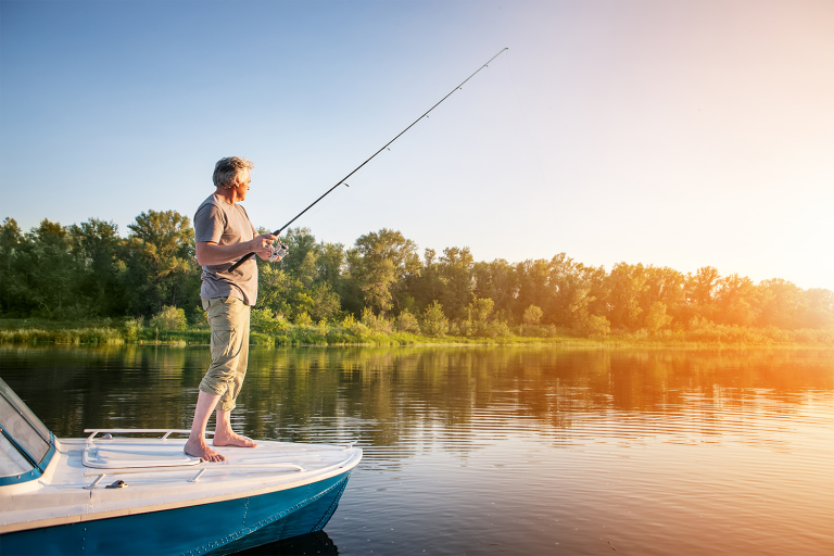 Boat and fishing gear storage. Photo is of a man wearing rolled up pants and a t-shirt standing on the bow of a boat, holding a fishing rod, looking over the water of a river