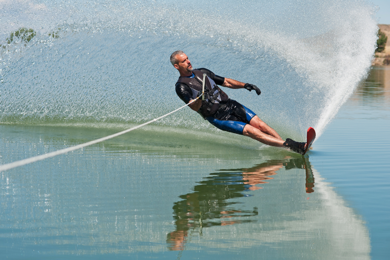 Man waterskiing. He is on a 45 degree angle and is reflected on the surface of the water with a spray of water behind him